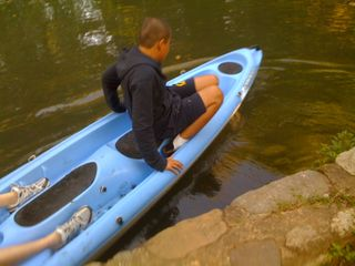 Charlie gets in the kayak in the river