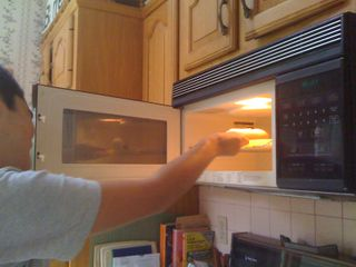 Charlie heating up a hot dog in the microwave oven