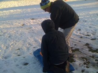 Jim helps Charlie get on the sled