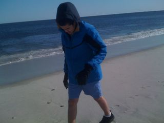 Charlie on a beach in winter and summer garb