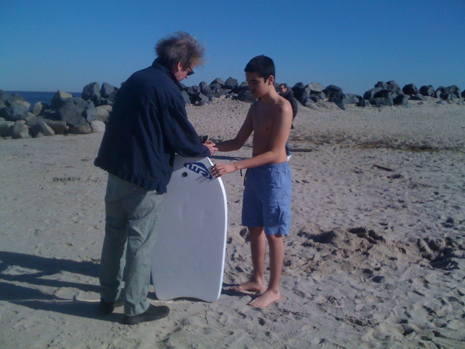 Jim helping Charlie fasten on the strap to his boogie board last Saturday