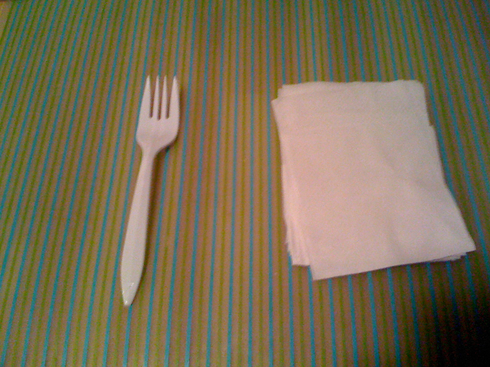 Fork, napkins, striped plastic placement arrangement by Charlie