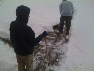 Charlie holding a snow shovel, Jim shoveling