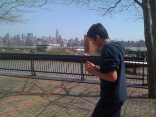 Charlie walking on the Hoboken waterfront across from midtown Manhattan and the Empire State Building