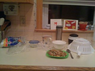 Arrangement, with shrimp lo mein and marshmallows and saran wrap on the kitchen counter, by Charlie