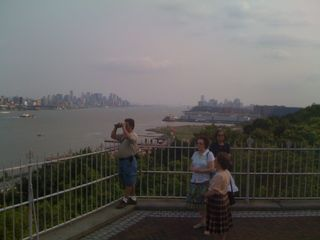 Lower Manhattan on the left, Jersey City on the right, three women in the foreground