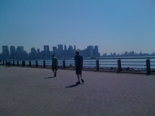 Charlie and Jim walking in Liberty State Park, with lower Manhattan and Brooklyn in the background