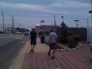 Jim and Charlie walking down a street at the beach