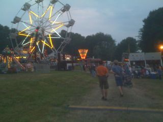 Charlie and Jim walking towards a firemen's carnival ferris wheel