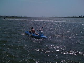 Charlie and Jim kayaking in choppy waters and perfect sunlight