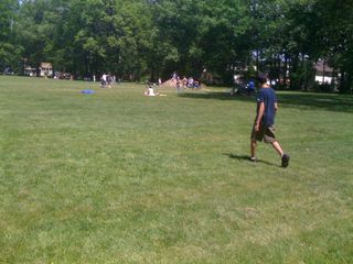 Charlie crossing a field where a soccer game is going on