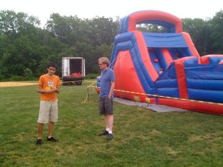 Charlie and Jim beside the inflatables at the school carnival