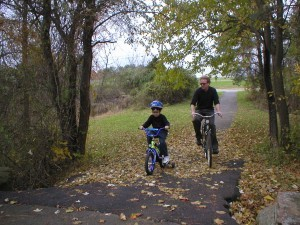 Charlienov02-Jim and Charlie biking by our condo in November of 2002